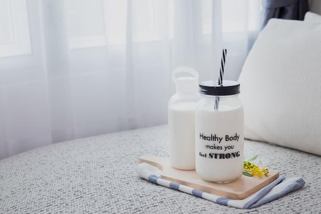 Una botella de leche y un vaso de leche en la cama en la sala con ventanas de cortina blanca.