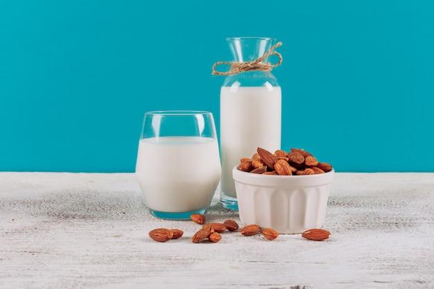 Botella de leche con un vaso de leche y un tazón de almendras vista lateral sobre un fondo blanco de madera y azul
