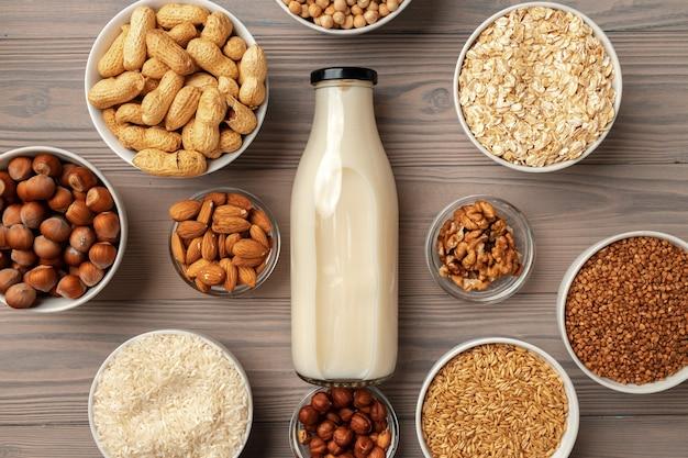 Botella de leche de vidrio y productos a granel sobre fondo de madera