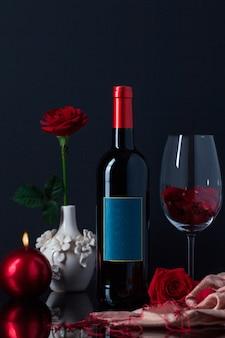 Botella de licor con copa, vela y rosa en florero