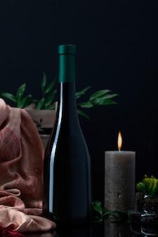 Botella de licor con vela, bufanda y planta en maceta