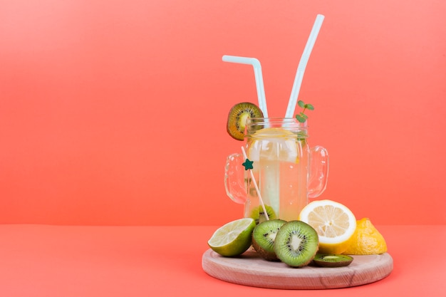 Botella de limonada con fruta cortada.