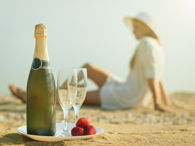 Una botella llena de chamán, fresas y la mujer en la playa.