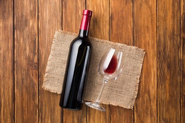 Botella llena de vino tinto y vaso vacío.