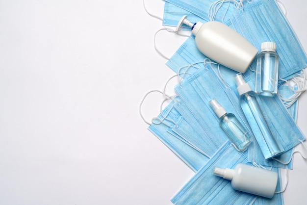 Botella de loción, desinfectante o jabón líquido y máscara protectora sobre fondo gris claro.