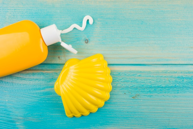Botella de loción de protección solar y vieira de plástico amarillo en el escritorio de madera turquesa