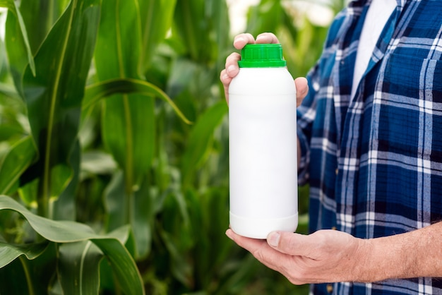 Botella en manos del granjero. botella sin etiqueta en blanco