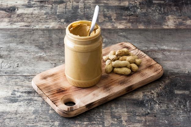 Botella de mantequilla de maní cremosa en mesa de madera