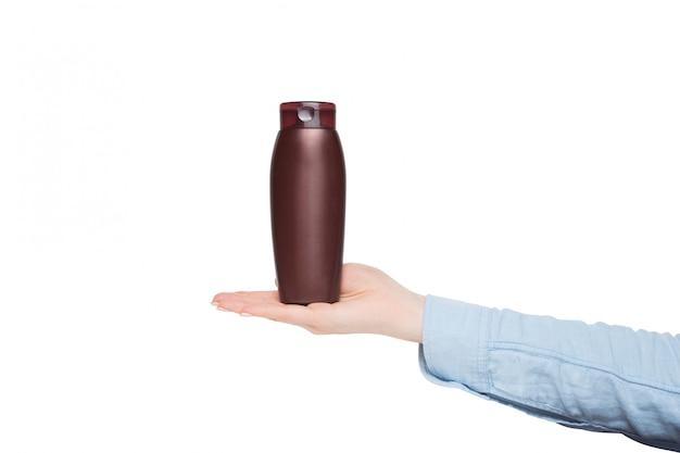 Botella marrón para cosméticos en una mano femenina, maqueta, aislar