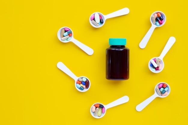 Botella de medicina con píldoras de medicina, tabletas y cápsulas en cuchara blanca, fondo amarillo.