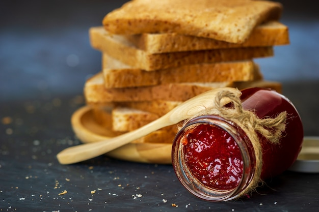 Botella de mermelada de fresa y pan integral se apilan