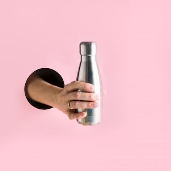 Botella de metal reutilizable en mano femenina a través de agujero rosa.