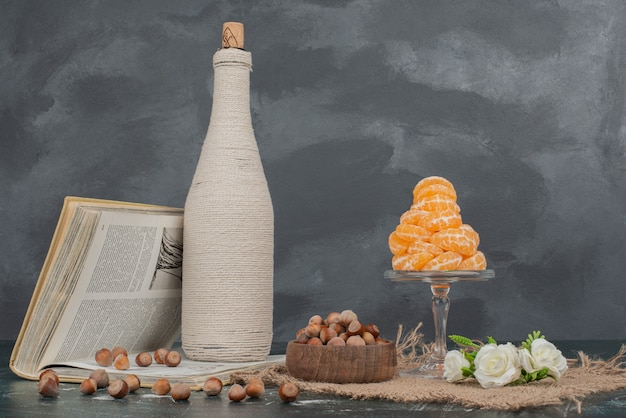 Botella con nueces y plato de cristal de mandarina.