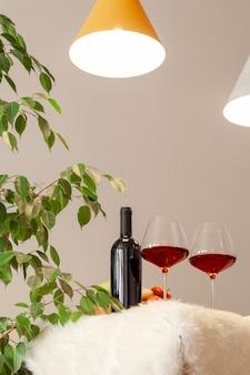 Botella oscura y dos copas de vino tinto, cuenco de madera con manzanas, jarrón de decoración en la mesa de la cocina moderna