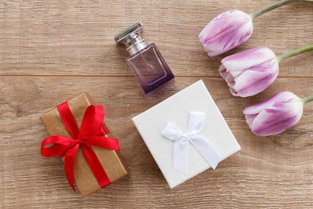 Botella de perfume y cajas de regalo sobre tablas de madera con tulipanes lilas