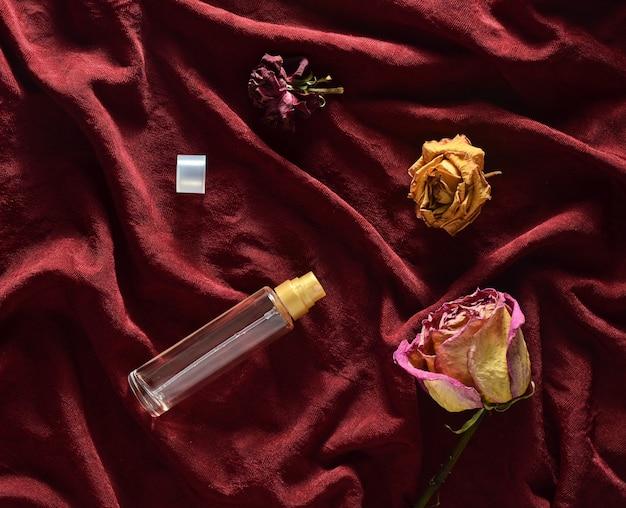 Una botella de perfume y capullos de rosas secas sobre seda roja. aspecto romántico vista superior.