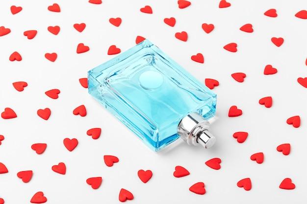 Botella de perfume con corazones rojos.