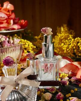Botella de perfume con especias y rodajas de naranja sobre fondo oscuro