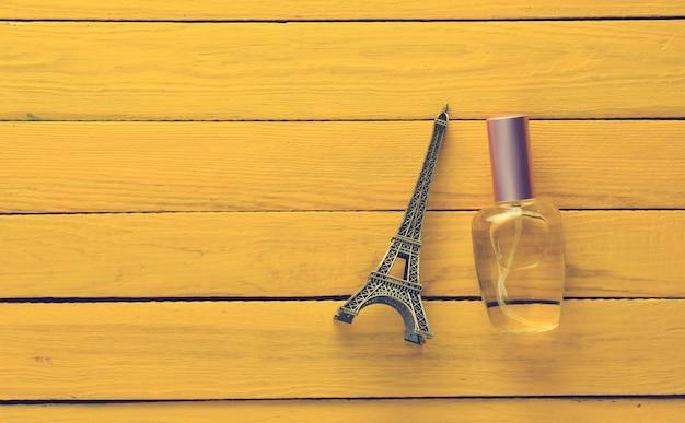Una botella de perfume y una estatuilla de recuerdo de la torre eiffel sobre una superficie de madera amarilla