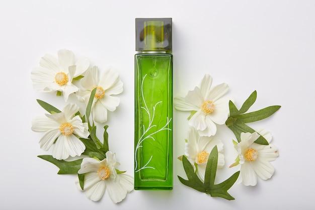 Botella de perfume con flores aisladas sobre blanco