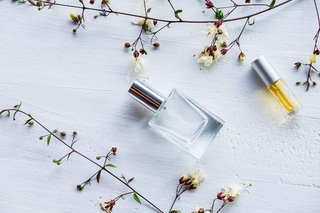 Botella de perfume con flores sobre un fondo blanco de madera
