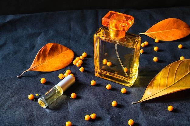Botella de perfume y perfume de oro sobre un fondo negro