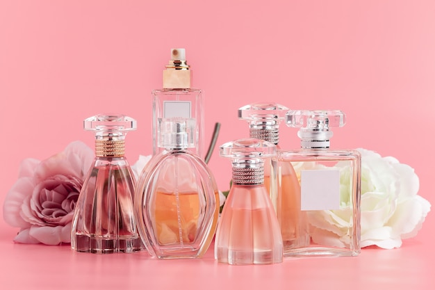 Botella de perfume con rosas sobre tela rosa