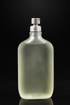 Botella de perfume sobre una superficie oscura.