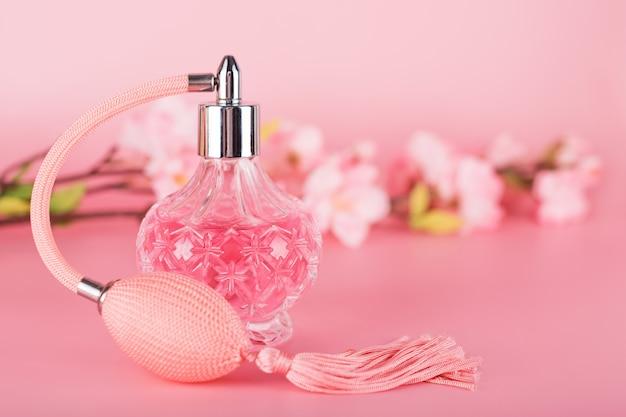 Botella de perfume transparente con rama de árbol floreciente primavera sobre fondo rosa