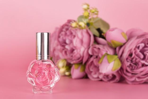 Botella de perfume transparente con ramo de peonías sobre fondo rosa. botella de esencia aromática