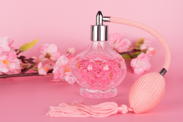 Botella de perfume de vidrio transparente con rama de árbol floreciente primavera sobre fondo rosa. botella de esencia aromática