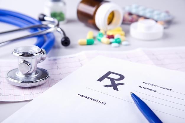 Botella de píldoras y estetoscopio médico en tabla de cardiograma