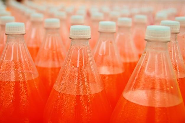 Botella plástica de la bebida del zumo de naranja en fábrica