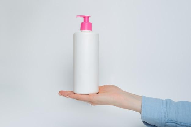 Botella plástica cosmética blanca con bomba en mano femenina