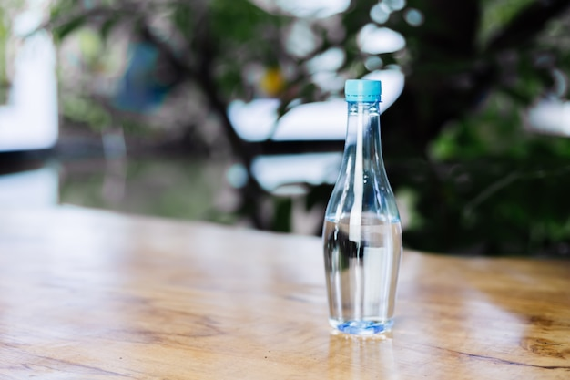 Botella de plástico de agua sobre la mesa de madera