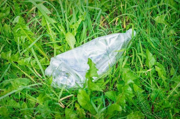 Botella de plástico arrugado tumbado en la hierba verde