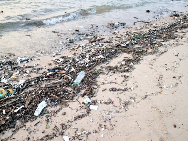 Botella de plástico de bambú y residuos de contaminación en playa.