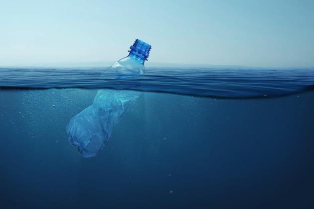 La botella de plástico de basura flota en el agua de mar azul bajo el agua. contaminación del medio ambiente y océanos.
