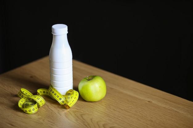 Botella de plástico blanco con una cinta métrica y una manzana verde sobre una mesa de madera con fondo negro