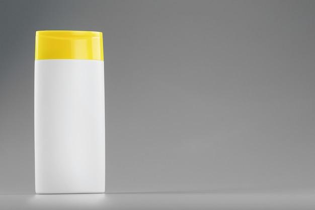 Botella de plástico blanco con tapón amarillo con gel de champú sobre superficie gris