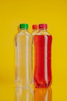 Botella de plástico llena de bebida sobre un fondo amarillo brillante