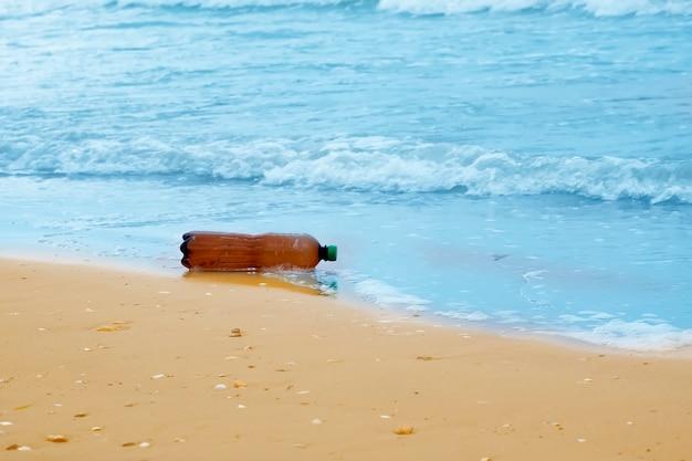 Botella de plástico en la playa, contaminación del mar.