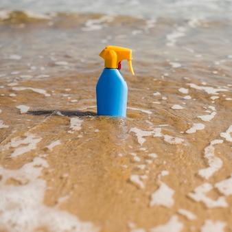 Botella de plástico protector solar azul en el agua de mar poco profunda en la playa