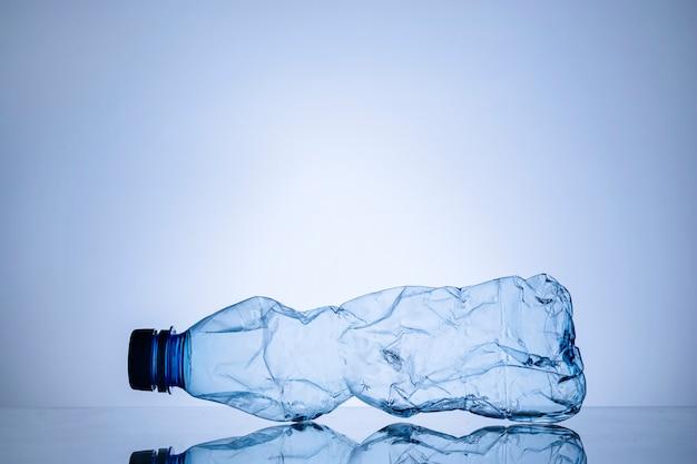 Botella de plástico transparente vacía arrugada en azul