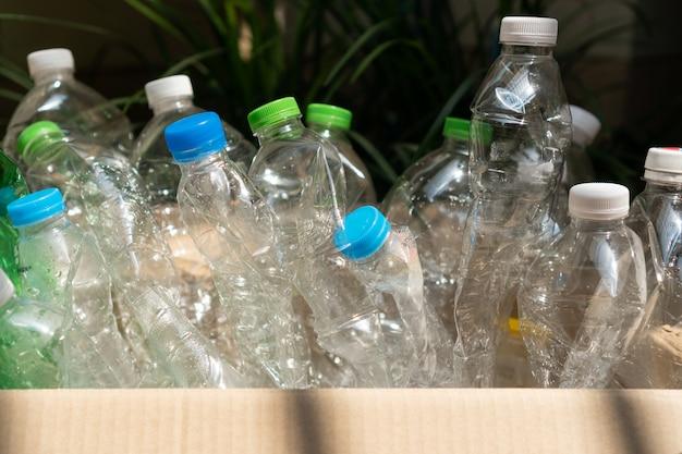 Botella de plástico usada en la caja, concepto de utilización de plástico reciclado. problema ecológico, contaminación ambiental. de cerca