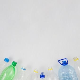 Botella de plástico vacía en la parte inferior del fondo blanco.