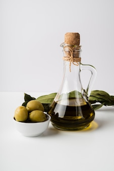 Botella de primer plano de aceite de oliva orgánico y aceitunas