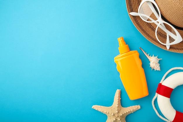 Botella de protección solar con sombrero, gafas y otros accesorios sobre fondo azul.