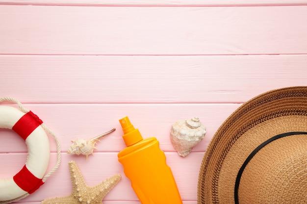 Botella de protección solar con sombrero, gafas y otros accesorios sobre fondo rosa.