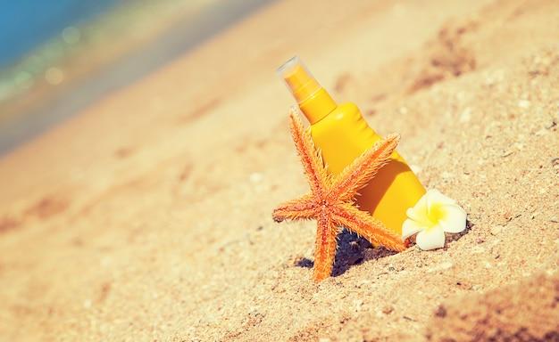 Botella de protector solar y una estrella de mar en la playa